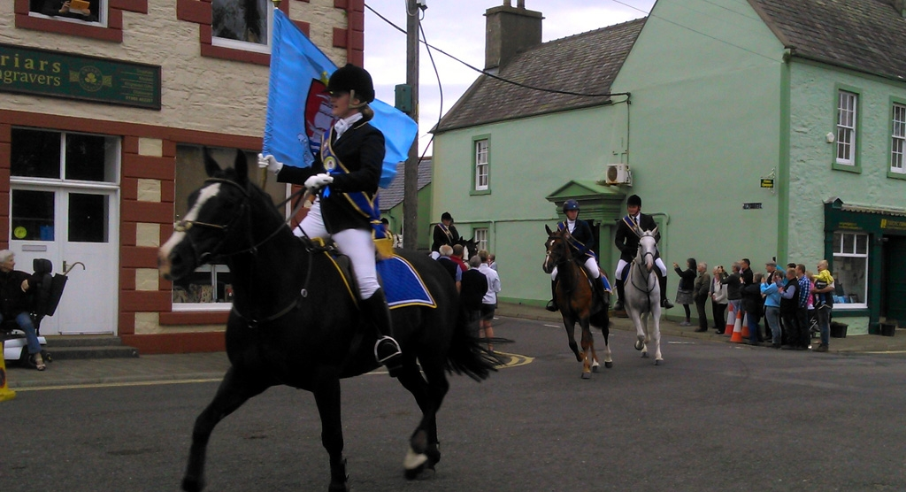 Photo of horses riding back into Wigtown.  The lead horse carrying the ensign flag.